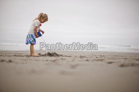 junges maedchen mit einer giesskanne spielen