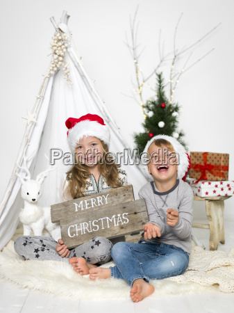 bruder und schwester mit weihnachtsmuetze