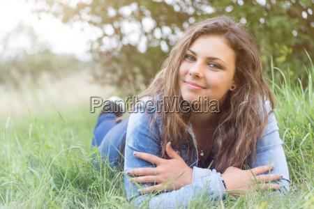 coole teenager maedchen liegt im gras