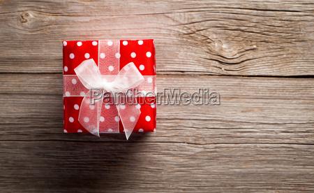 rotes geschenk auf einem hoelzernen hintergrund