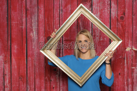blond girl looks through a picture