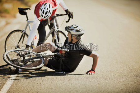 reifer mann faellt beim radfahren um