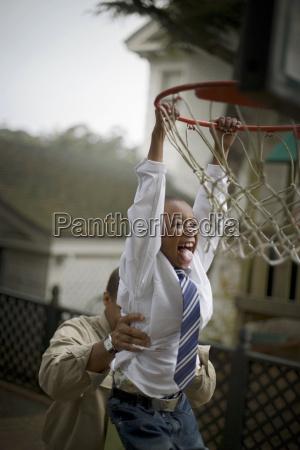 lachender junge von einem basketballkorb haengt