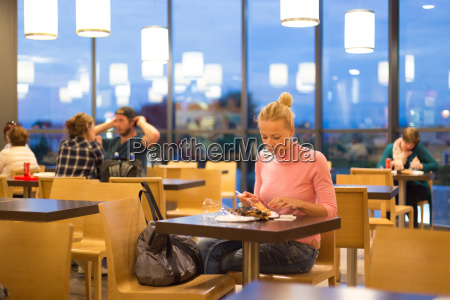 young woman eating pizza at airport