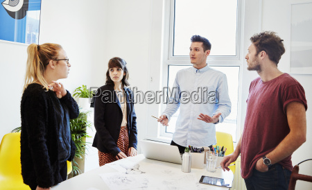 four people standing around a table