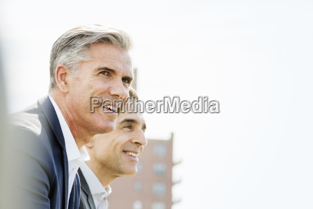 two people men talking together outdoors