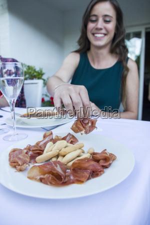 frau nimmt ein stueck spanischen schinken