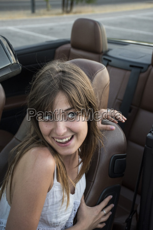 smiling young woman sitting in convertible