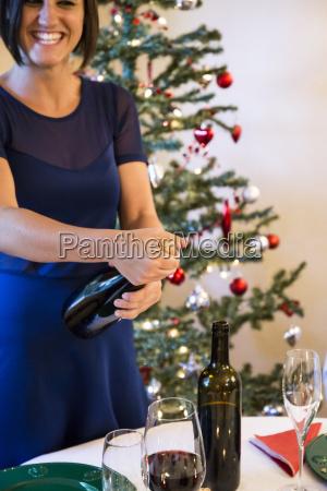 frau lacht beim OEffnen einer flasche