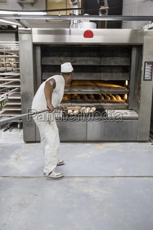 baecker nimmt frisch gebackenes brot aus
