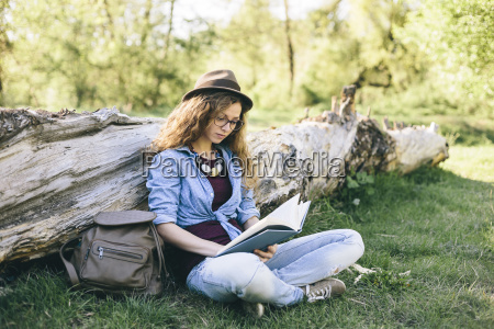 woman sitting on a meadow reading