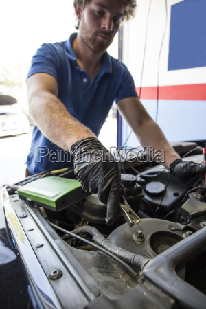 mechanic placing a battery clip in
