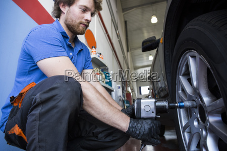 mechanic fixing a car wheel in