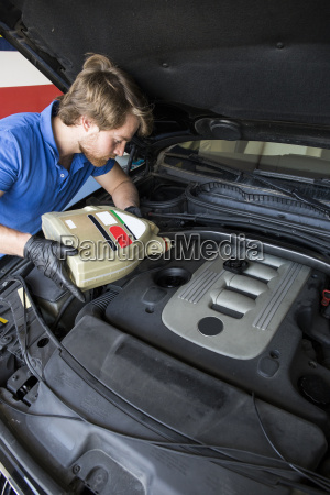 mechanic refilling oil in a car