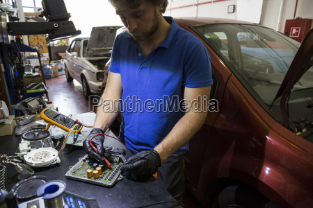 mechanic fixing an electronic car parts
