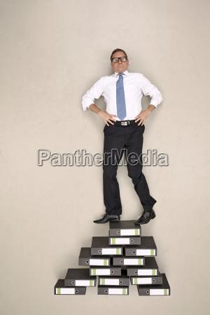 businessman standing on file folders