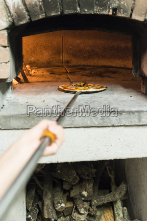 putting pizza in traditional oven