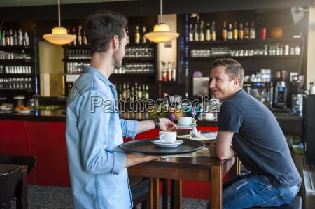 kellner serviert cappuccino in einem cafe