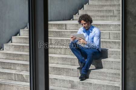 businessman sitting on stairs looking at
