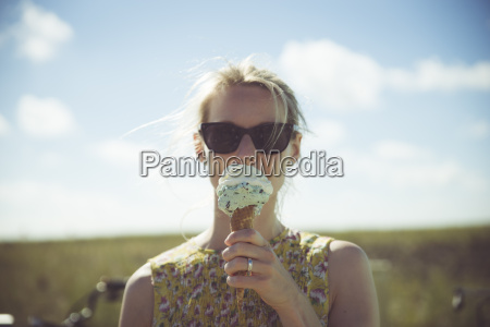 blond woman with sunglasses eating ice