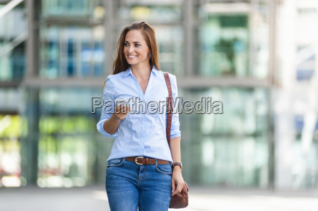 smiling woman with cell phone outdoors