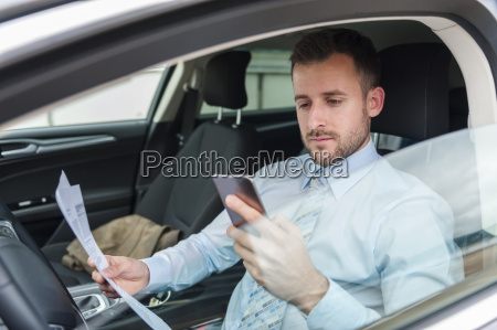 businessman with documents and cell phone