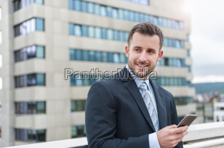 smiling businessman with cell phone in