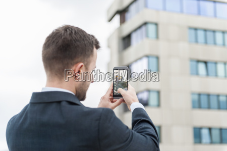 businessman taking a cell phone picture