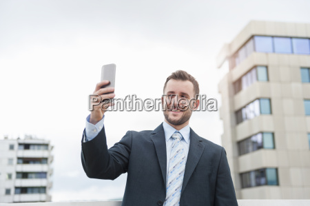 smiling businessman taking a selfie in