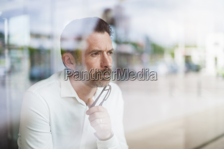 portrait of serious businessman looking through
