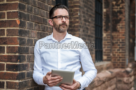 portrait of businessman with tablet leaning