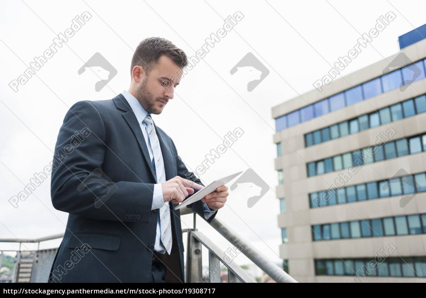 geschäftsmann, mit, blick, auf, digitales, tablet - 19308717