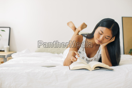 young woman lying in bed reading