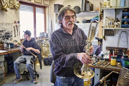 instrumentenbauer pruefen trompete in werkstatt