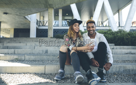 smiling young couple sitting on steps
