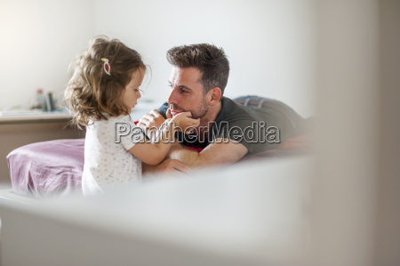 father and daughter on bed