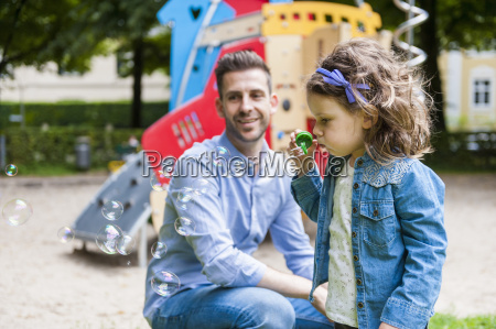 daughter with father on playground blowing