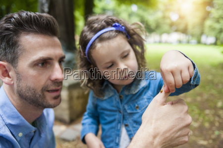 father and daughter examining ladybird on