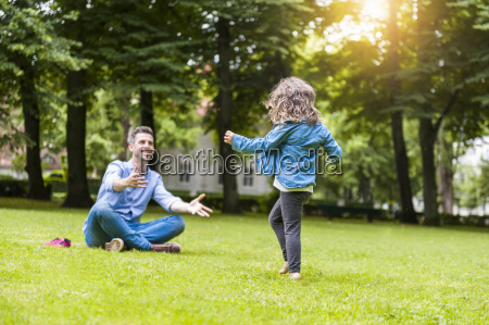 father and daughter playing on meadow