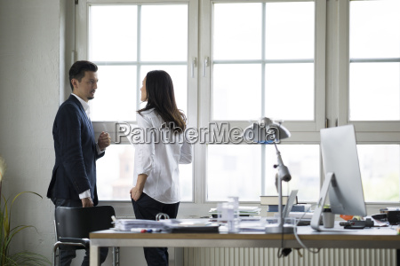 businessman and woman standing at office