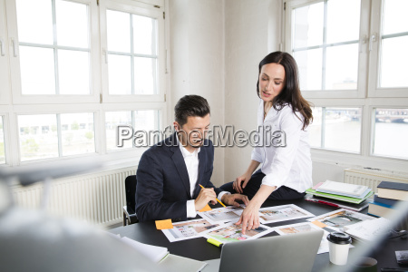 businessman and woman sitting at desk