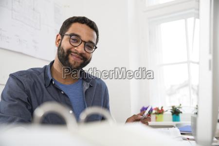 portrait of smiling man at desk