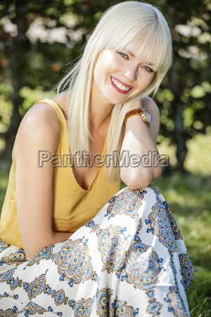 portrait of smiling blond woman sitting