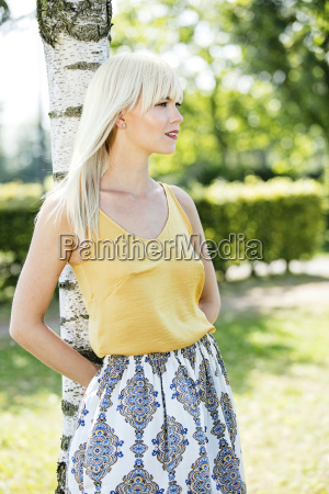 blond woman leaning against tree trunk