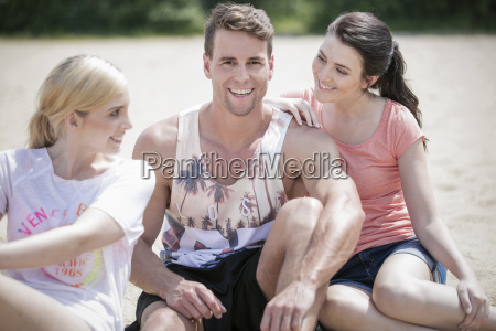 three friends sitting on the beach