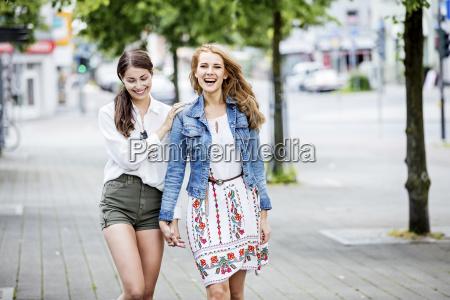 two happy young women walking in