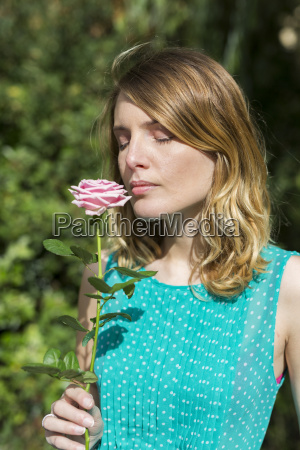 portrait of young woman smelling rose