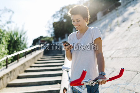 smiling young woman with bicycle and