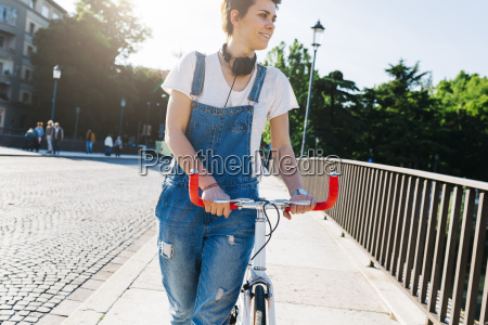 smiling young woman pushing bicycle on