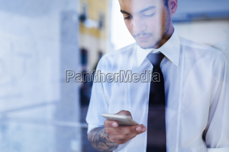 young businessman behind glass pane looking
